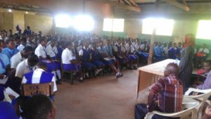 A lady in a hall standing, addressing students