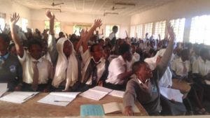 School girls seated and some raising hands, an indication of answering or asking a question.