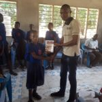 Our founder presenting the gift of a book to a student who has excelled.